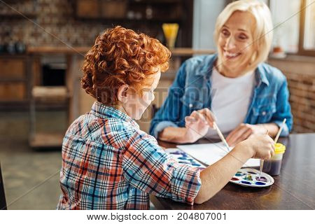 He is so cute. Selective focus on a turned redhead boy sitting next to his beaming grandmother and painting a new masterpiece while both chatting and having fun.
