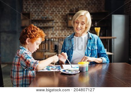 Calmness and serenity. Selective focus on a concentrated curly haired boy sitting next to his positive minded granny and painting an abstract picture while both spending free time at home.