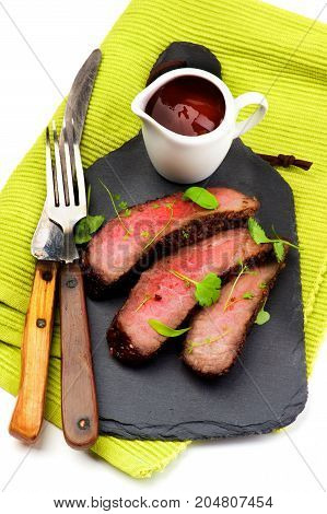Slices of Roast Beef Medium Rare on Slate Serving Board with Tomato Sauce Fork and Table Knife on Green Napkin closeup