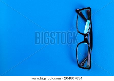 Modern fashionable and office spectacles on blue background Perfect reflection eye glasses on table for copy space.