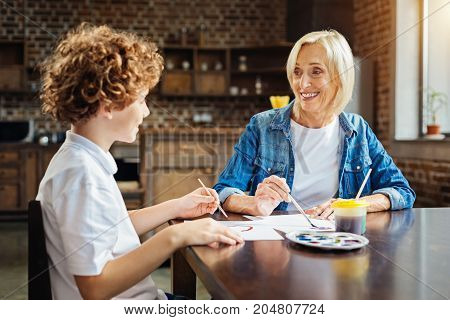 You are joking. Thoughtful elderly woman grinning broadly while painting with her grandchild and listening to his stories at a family dinner table.