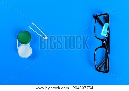 Contact lenses set with plastic case and tweezers with glasses on the background plan on a lilac background. How to store and use contact lenses.