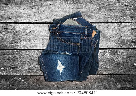 Casual jeans on the wooden background. Top view