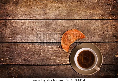 Cup of coffee with croissant. Top view