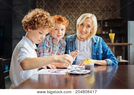 I am so proud of them. Selective focus on smiling senior woman and her adorable redhead grandchild looking into the camera while sitting next to her another grandson during a family painting session.