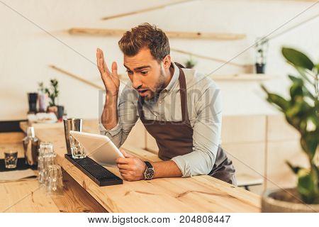Barista Using Tablet In Coffee Shop