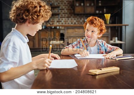 Two peas in a pod. Selective focus on a happy redhead boy looking at his older brother with an exited smile on his face while both spending free time together and drawing.