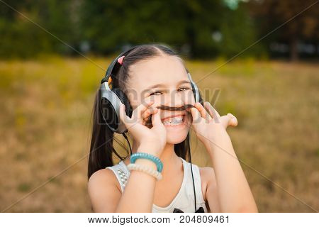hipster funny girl having fun shows moustache hair over field. child listening music with headphones