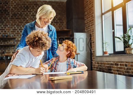 Heartwarming stories. Selective focus on an elderly woman smiling while standing next to her grandchildren and listening to one of them telling her something amusing while drawing with pencils.