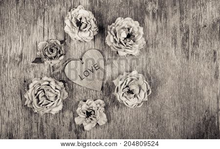 Dry roses and a wooden heart. Dead flowers and love. Romantic concept. Monochrome