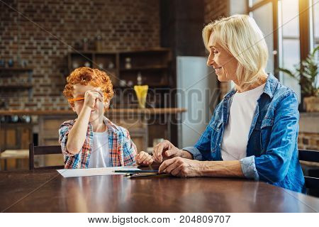 Love him to the moon and back. Elderly lady sitting next to her redhead little grandchild and looking at him with a smile on his face while he drawing with pencils and joking.