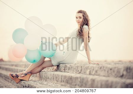 beautiful woman with flying multicolored balloons sitting and dreaming against the sky. soft light