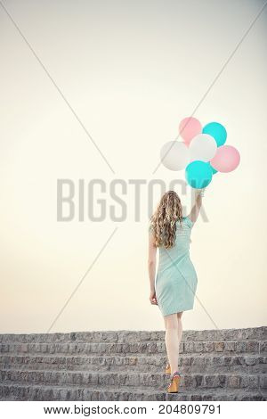 young beautiful woman with flying multicolored balloons against the sky.  soft light