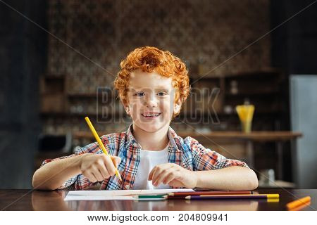 I am so happy right now. Portrait of a redhead boy looking into the camera with a cheerful smile on his face while sitting at a table and drawing with colorful pencils.