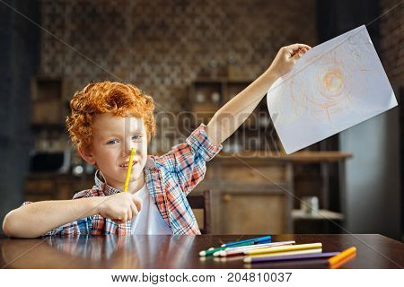 Look what I drew. Blue eyed child wearing a plaid shirt touching his nose with a colorful pencil while sitting at a table and showing his abstract picture into the camera.