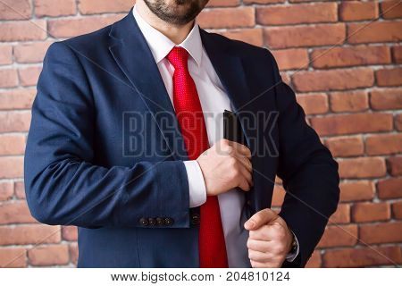 Businessman in a red tie hides a black purse in his jacket pocket