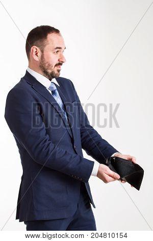surprised businessman in blue suit shows an empty black wallet