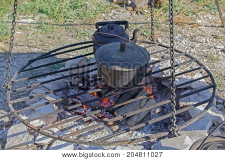 big black kettle on the grate over fire