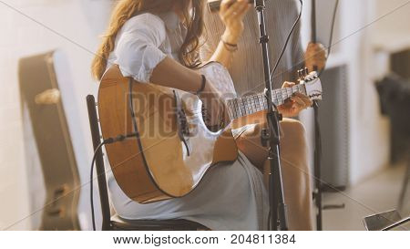 Woman with guitar at stage in loft - rock band - hipster's music