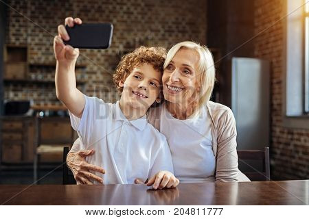 One more shot. Beaming elderly lady embracing her preteen grandchild while both sitting at a table and taking selfies while spending some time together.