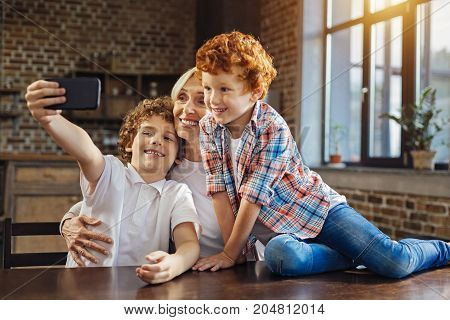 Family memories. Selective focus on a beautiful elderly woman and a chestnut haired boy grinning broadly while looking at a front camera of a phone and taking selfies at home.