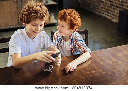 I like this one. Selective focus on an excited ginger haired boy grinning broadly and talking to his older brother while both wearing earphones and enjoying the music playing.