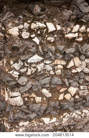 Old road paved with stones. Stone pavement as the background texture