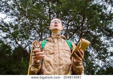 Image from below of man with compass and notepad in autumn forest during day