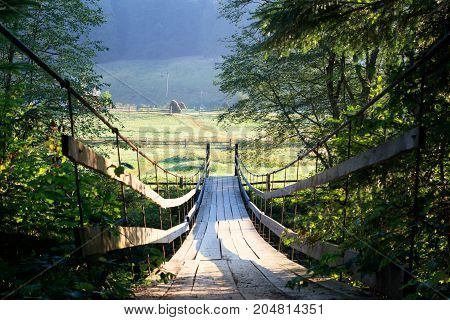 suspension bridge across the river. morning time. Stack of hay on the glade on the other side of bridge. green trees