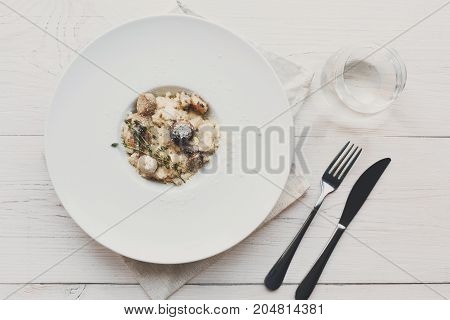 Wild mushrooms porcini risotto with rosemary and grated parmesan cheese. Traditional italian cuisine dish. Restaurant food closeup. Forest fungus with rice, top view