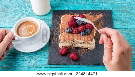 Tiramisu cake with raspberries and blueberries. Homemade tiramisu dessert. Traditional Italian cuisine