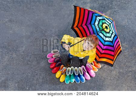 Little kid boy and group of colorful rain boots. Blond child standing under umbrella. Close-up of schoolkid and different rubber boots from high angle. Footwear for rainy fall.