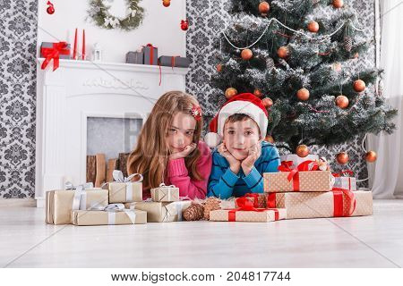 Beautiful children portrait with christmas present boxes on holiday morning in beautiful room interior. Boy and girl got Xmas gifts near decorated fir tree and fireplace. Winter holidays concept
