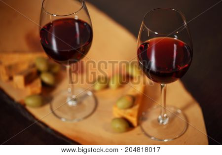 Wineglasses With Red Wine On Wood With Cheese And Green Olives - For Cozy Home Evening
