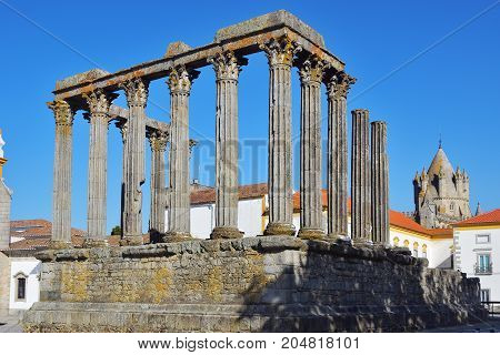 Roman ruins of Diana's Temple. The dome of the cathedral in the background. Evora Portugal