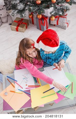 Writing letter to santa. Children in santa hats make wish list of presents for christmas. Winter holidays. Boy and girl, brother and sister draw