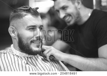 Monochrome shot of a handsome young man smiling cheerfully while getting a new haircut at the local barbershop.