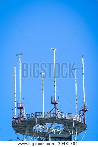 mobile phone antenna in a building against blue sky with clouds