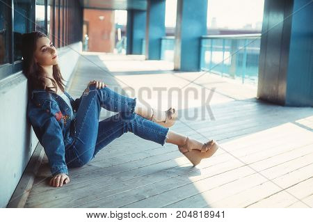 beautiful girl sitting on the floor of the train station. young woman in denim clothes sitting on the street. copy space for your text