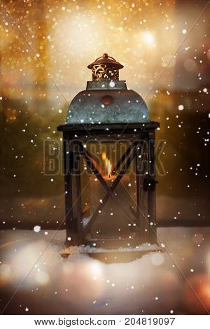 Winter still life with a burning lantern in the snow for christmas time