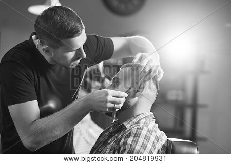 Monochrome shot of a professional barber shaving his client.
