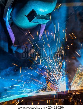 Industrial worker is welding car part in factory