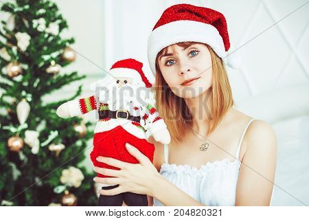 Pretty girl holding Santa Clause plush toy. Smiling woman holding small Santa Claus. Father Christmas toy in girl's hands. Holiday season and Christmas concept
