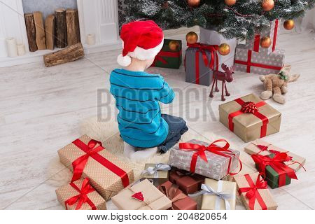 Cute happy boy in santa hat unwrap christmas present box on holiday morning in beautiful room interior. Male child sitting with his back to camera near fir tree and fireplace. Winter holidays concept