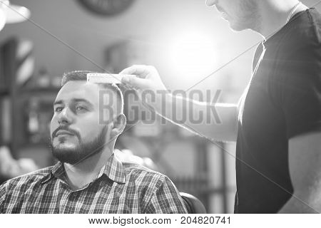 Black and white shop of a bearded man getting his hair styled by a barber copyspace.