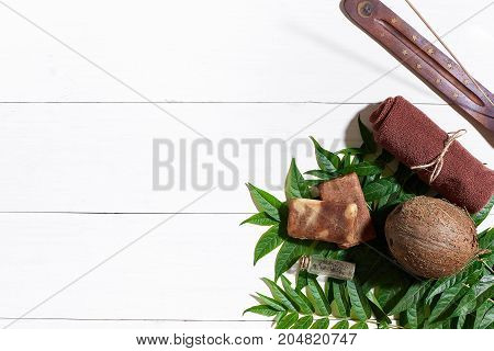 Brown towel, blue clay and natural coffee soap on white wooden table, top view. Still life. Close-up. Flat lay. Copy space