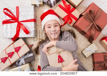 Happy girl child in santa hat lay on warm carpet among Christmas gift boxes. Xmas holiday concept. Top view of excited beautiful female kid got lots of presents
