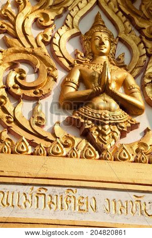 Pattaya Thailand - March 25 2016: Golden figure of Buddha god carved on an Asian Buddhist shrine. Beautiful ornamental decoration with some religious text inscribed on a Thai temple