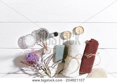 Spa products. Bath salts, dry flowers lavender, soap, candles and towel. Aroma sticks, aromatherapy. Flat lay on white wooden background, top view. Still life. Close-up. Copy space