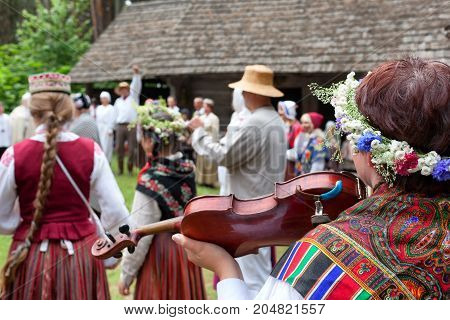 People in Latvian national costumes are dancing on the street in the countryside in summer